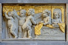 Flachrelief im Stein und im Gold von Engeln in einer Textilwerkstatt Lizenzfreies Stockbild