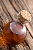 Flacon de cristal con aceite en la madera vieja Fotografía de archivo