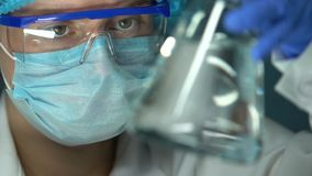 Flacon de participation de technicien de laboratoire médical avec le liquide transparent, vérifiant la qualité de l'eau banque de vidéos