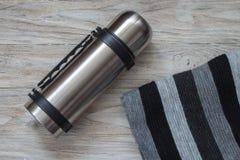 Flacon et écharpe de thermos sur un fond de woden Vue supérieure Images stock