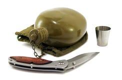 Flacon et couteau militaires en métal sur le blanc Images libres de droits