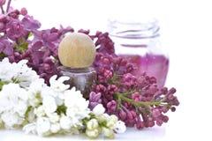 Flacon parmi des fleurs de lilas rose et blanc Image stock