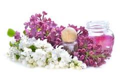 Flacon parmi des fleurs de lilas rose et blanc Images stock