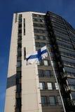 Fladderende nationale vlag van Finland naast de moderne bouw Royalty-vrije Stock Afbeeldingen