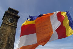 Flag. The Buddhist flag flies near the old clocktower at Galle, Sri Lanka Stock Images