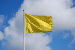 Flag. Yellow empty flag with a blue sky, caution and danger Royalty Free Stock Photo