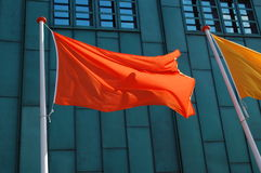 Flag. Empty orange flag with a building in the background Stock Image