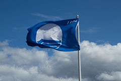 Flag. Showing the symbol for clean beach flaps in the wind with a blue sky and cloud Stock Photography
