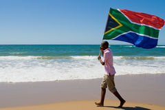Flag. African man running on beach with a south african flag, new south africa 2010 world cup concept royalty free stock photography