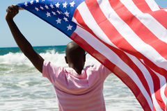 Flag. Young african american man waving  USA flag on beach Stock Photo
