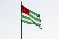 Flag of Abkhazia waving on wind. The Abkhazian flag against the background of the sky Stock Image