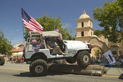 Flag adorned jeep demonstrates 4 wheel maneuvers as it makes its way down main street during a Fourth of July parade in Ojai, CA Royalty Free Stock Image