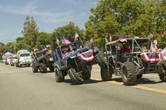 Flag adorned jeeps demonstrate 4 wheel maneuvers as they make their way down main street during a Fourth of July parade in Ojai, C Royalty Free Stock Images