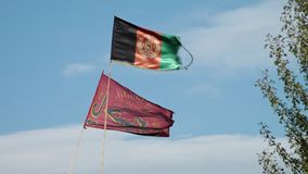 The flag of Afghanistan. A hand held, low angle, medium shot of the flag of Afghanistan and another red Muslim flag moving in the windy day stock video footage