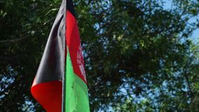 The flag of Afghanistan. A hand held, panning, extreme close up shot of the flag of Afghanistan, while it dances in the wind of the day stock video footage