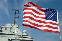 Flag & Aircraft Carrier. American flag flying with part of the aircraft carrier Yorktown in the background stock image