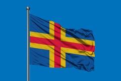Flag of Aland Islands waving in the wind against deep blue sky vector illustration
