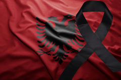 Flag of albania with black mourning ribbon. Waving national flag of albania with black mourning ribbon royalty free stock photo