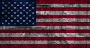 Flag of America on background stone wall texture. Closeup Stock Photo