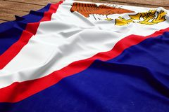 Flag of American Samoa on a wooden desk background. Silk flag top view royalty free stock photo