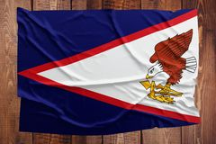 Flag of American Samoa on a wooden table background. Wrinkled Samoan flag top view.  stock photos