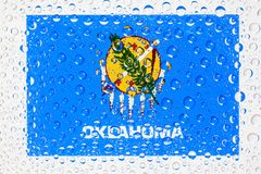Flag of American State Oklahoma behind a glass covered with rain. Drops. Patriots day, memorial weekend, veterans day, presidents day, independence day Royalty Free Stock Photography