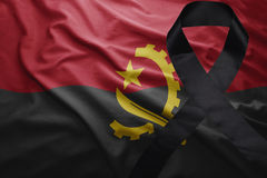 Flag of angola with black mourning ribbon. Waving national flag of angola with black mourning ribbon Stock Images