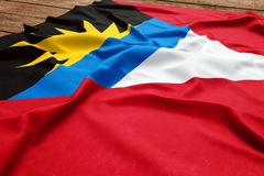 Flag of Antigua and Barbuda on a wooden desk background. Silk Antiguans-Barbudans flag top view.  stock photos