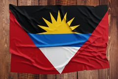 Flag of Antigua and Barbuda on a wooden table background. Wrinkled flag top view royalty free stock image