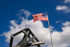 Flag With Art. An American Flag waving in the wind with public modern art in the foreground stock photo