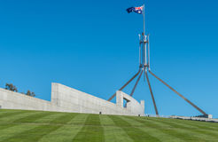 Flag atop the Australian Parliament Building. The large Australian flag flying over the landmark Parliament Building in Canberra Stock Images