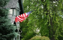 Flag attached to home. US flag hung from traditional looking multi-story home Royalty Free Stock Photography