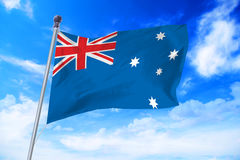 Flag of Australia developing against a blue sky Stock Photo