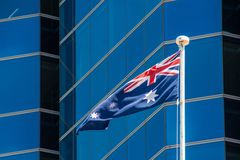 Flag of Australia waving in light breeze in front of modern skyscraper facade. Flag of Australia waving in light breeze in front of modern skyscraper stock images