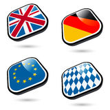 Flag Badges. Four badges with various country flag designs.  Isolated against a white background Royalty Free Stock Image