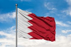 Flag of Bahrain waving in the wind against white cloudy blue sky. Bahraini flag royalty free stock photo