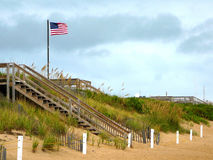 Flag on the Beach. A lone US flag waves in the wind of an approaching storm at the beaches of Corolla in the Outer Banks of North Carolina Royalty Free Stock Photo