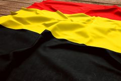 Flag of Belgium on a wooden desk background. Silk Belgian flag top view.  stock photography