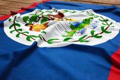 Flag of Belize on a wooden desk background. Silk Belizean flag top view.  stock image