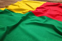 Flag of Benin on a wooden desk background. Silk Beninese flag top view.  stock photos