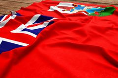 Flag of Bermuda on a wooden desk background. Silk Bermudian flag top view.  royalty free stock photography