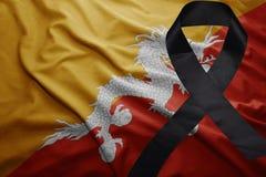 Flag of bhutan with black mourning ribbon. Waving national flag of bhutan with black mourning ribbon Stock Image