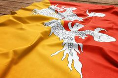 Flag of Bhutan on a wooden desk background. Silk Bhutanese flag top view.  royalty free stock image