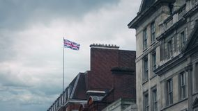 Typical London buildings with flag blowing. Flag blows around on rooftop on old London buildings stock video footage