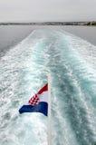 Flag and Boat. Croatian flag waving behind a passenger ship, water trail Royalty Free Stock Photos