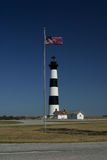 Flag Bodie Island Lighthouse. American flag waving near Bodie Island Lighthouse in North Carolina Stock Photos