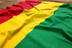Flag of Bolivia on a wooden desk background. Silk Bolivian flag top view.  stock image