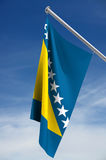 Flag of Bosnia-Herzegovina. A view of the national flag of Bosnia-Herzegovina hanging from a short white flagpole with blue sky and thin white clouds in the stock illustration