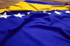 Flag of Bosnia and Herzegovina on a wooden desk background. Silk Bosnian flag top view.  stock photography