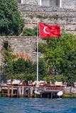 Flag on Bosporus strait. The Bosporus is a narrow, natural strait and an internationally significant waterway located in northwestern Turkey. It stock photography